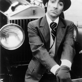 """1973: Drummer Keith Moon of the rock and roll band """"The Who"""" poses for a porrait wearing a 3 piece suit and hat as he sits on the bumper of a Rolls Royce in 1973. (Photo by Michael Ochs Archives/Getty Images)"""